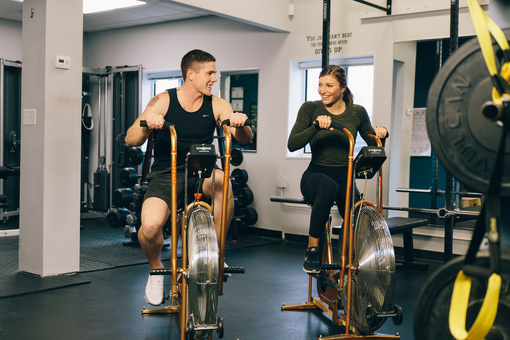 best cardio for weight loss at the gym - a man and a woman cycling at the gym