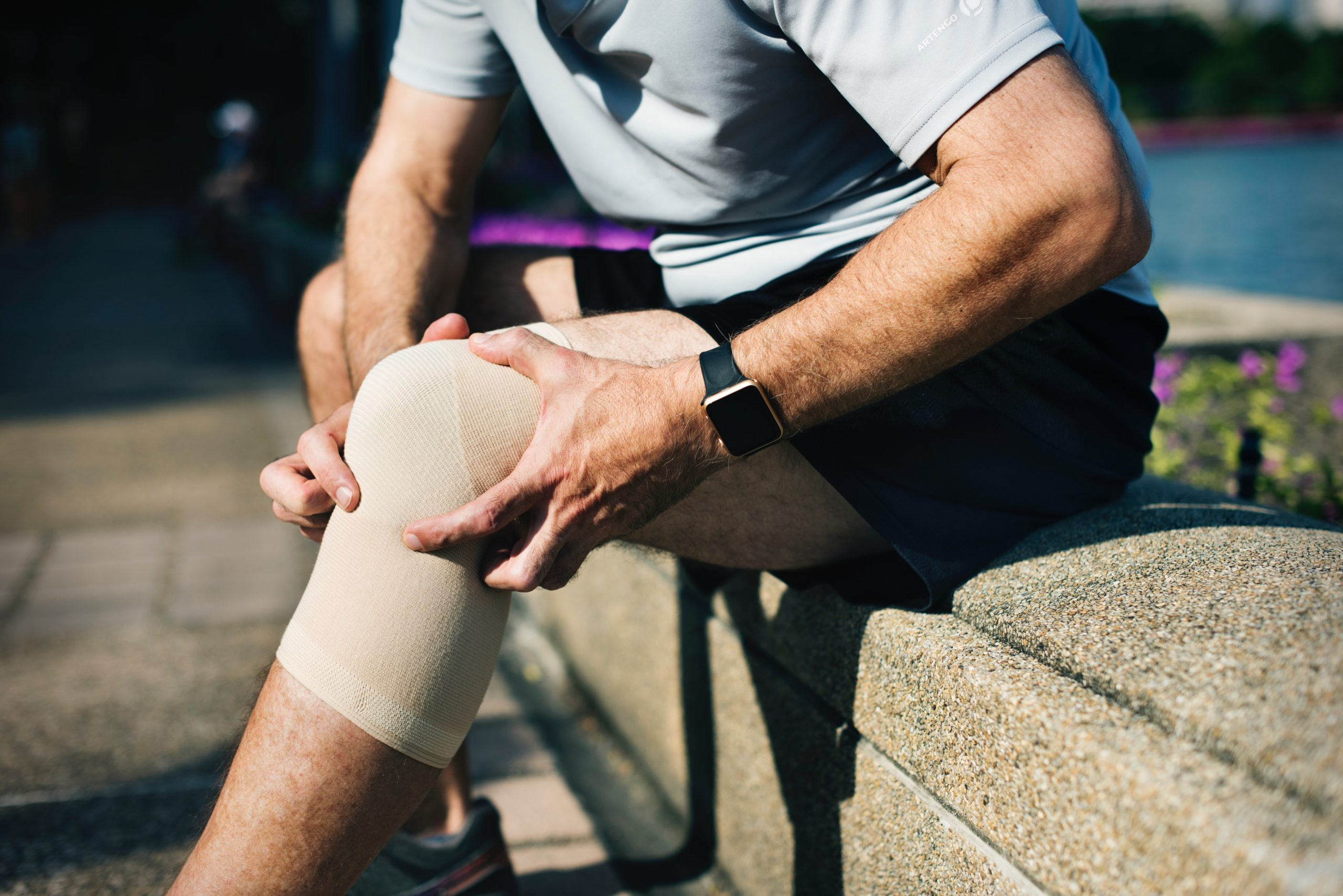 Injury rehabilitation programme for knee injuries: a man holding his injured knees