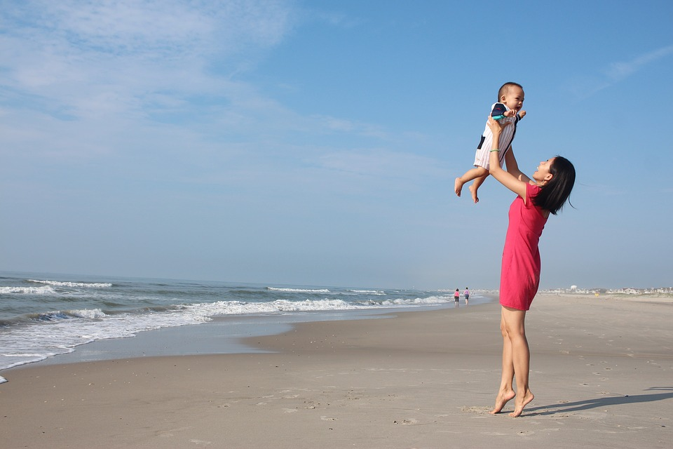 how to lose the baby weight, a mother holding her child on the beach