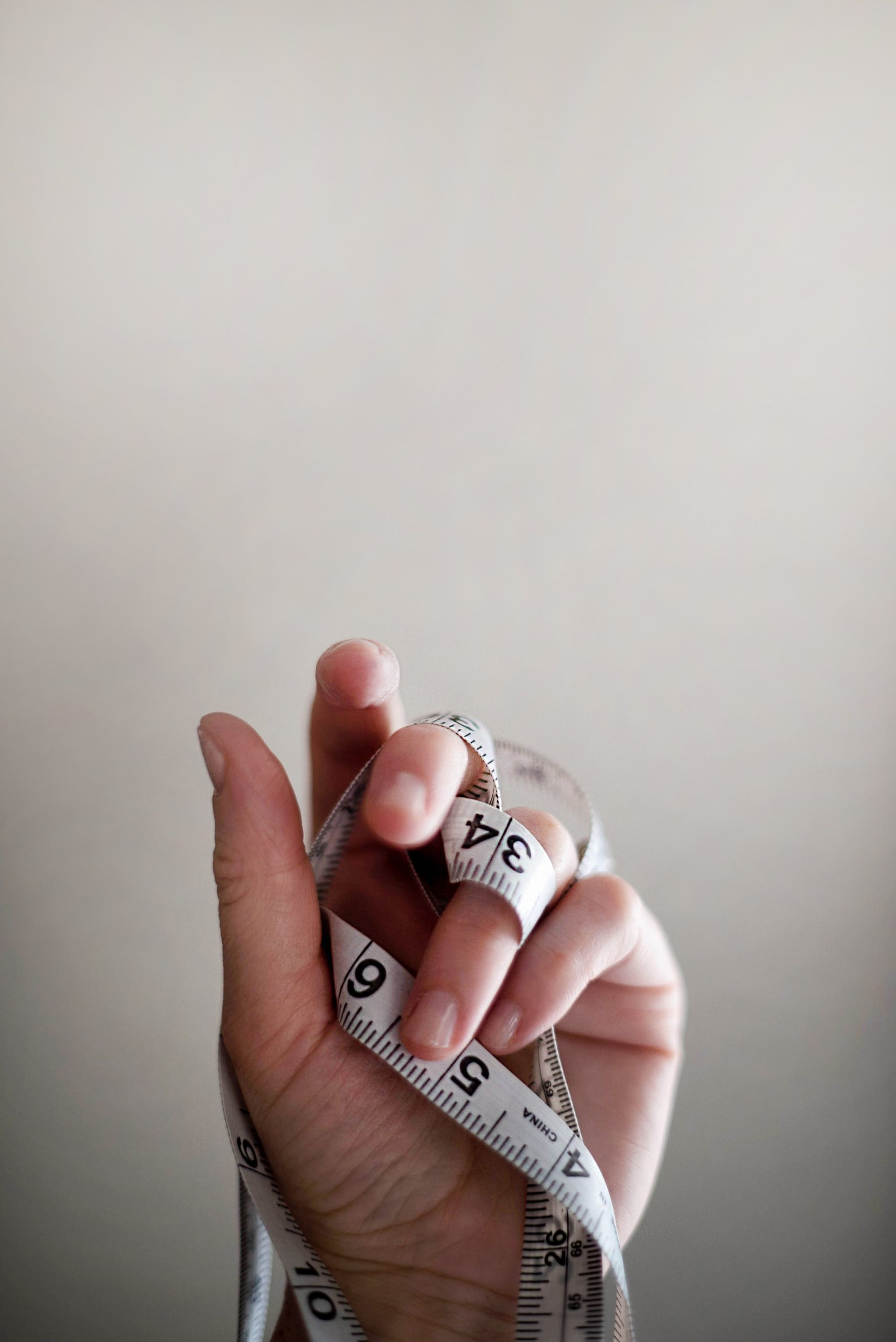 How to lose the Christmas weight; a picture of a hand holding a measure, indicating weight loss